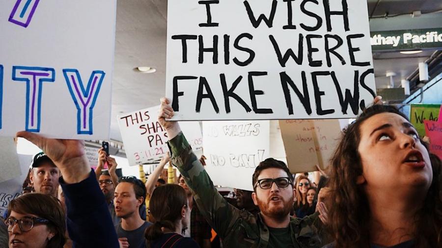 """En flok mennesker, hvor en holder et skilt, hvor der står:""""I wish this was fake news."""""""