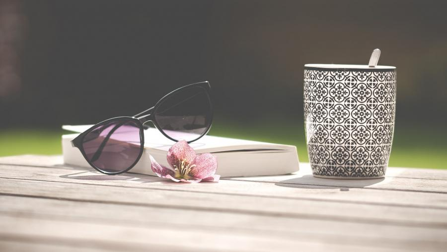 En bog med solbriller ovenpå og et kaffekrus ved siden af.